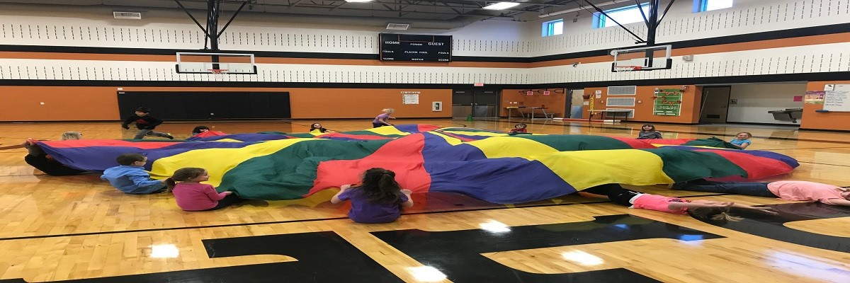 "Kindergartners play ""Shark Attack""  with a parachute in PE"