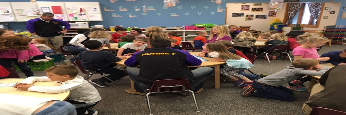 football players reading to students